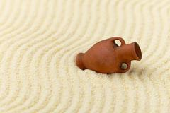 ancient clay amphora on surface of yellow sand - stock photo