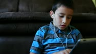 Close up of young boy learning on tablet wearing headphones Stock Footage