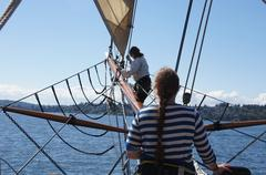 the crew rigs the sails - stock photo