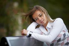 Beautiful girl sitting on the bench Stock Photos