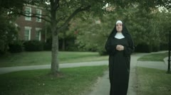 Nun walking down sidewalk side walk Stock Footage