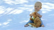 Baby boy nodding and holding a teddy bear toy Stock Footage