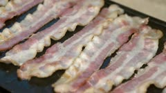 Bacon strips cooking on griddle Stock Footage
