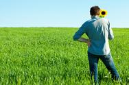 Young man standing with a sunflower in the green field Stock Photos