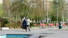 Old couple walking toghether in park Stock Footage