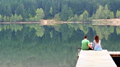 Young family sitting on the dock and looking to the lake - stock footage