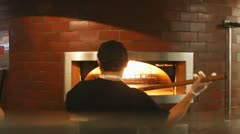 Man Using A Wood Fired Pizza Oven Stock Footage