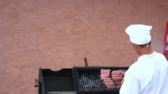 Cooker turning the sausages on the grill Stock Footage