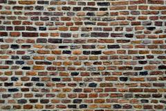 old parti-colored brick wall - stock photo