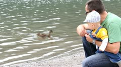 Father holding his baby boy and feeding the ducks Stock Footage