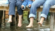 Baby and parents feet hanging on mountain lake pontoon Stock Footage