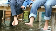 Barefoot parents and baby feet relaxing on a wooden pontoon Stock Footage