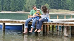 Young family spending time toghether on mountain lake pontoon Stock Footage