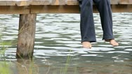 Lady feet hanging on a mountain lake wooden pontoon Stock Footage