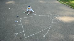 Baby drawing his mother with chalk on asphalt Stock Footage