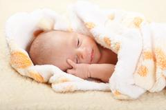Baby lying and holding his head. Stock Photos