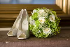 Wedding shoes and flowers bouquet Stock Photos