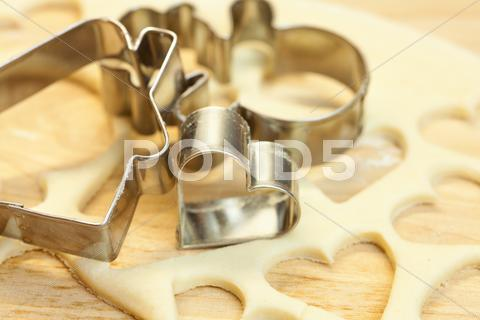 Stock photo of cut dough snowman, house, heart, and forms for cookies