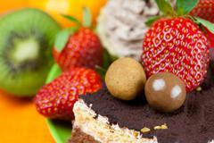 cake, chocolate candy, tangerine, kiwi and strawberries on the orange fabric - stock photo