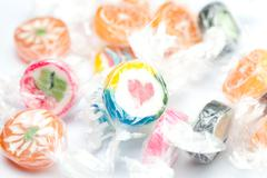 Background of multi-colored candies in shiny wrappers Stock Photos