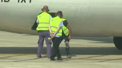 Airport worker closes airplane flap Stock Footage