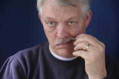 senior man using toothpick.jpg - stock photo