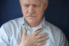 Older man feeling pain in chest.jpg Stock Photos