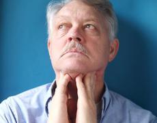 Man feeling painful lymph glands.jpg Stock Photos