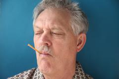 Feverish man with a thermometer.jpg Stock Photos