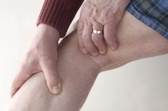 Man checks pain in his leg.jpg Stock Photos