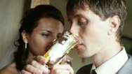 Groom with bride drink champagne kiss Stock Footage