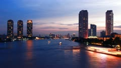 Stock Video Footage of Bangkok city at sunset with the evening twilight. The flurry of boats on the riv