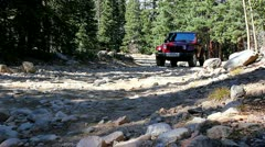 Jeep driving by on a rocky road in the beautiful Rocky Mountains - stock footage
