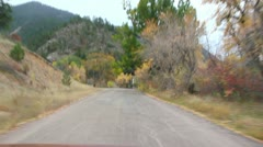 Driving past an old abandoned hotel on bumpy road in Beautiful Rocky Mountains Stock Footage