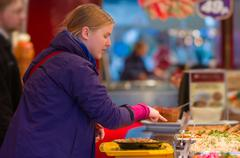 Young woman ordering dishes with vegetables and meat in restaurnat Stock Photos