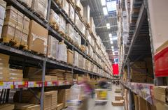 Rows of shelves with boxes in modern warehouse with customers walking Stock Photos