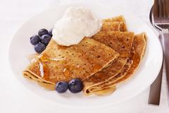 Stock Photo of pancakes with blueberries cream and maple syrup