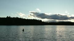 Swimmer wades in walden pond Stock Footage