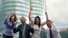 Excited, happy, successful businesspeople by skyscraper, slow motion HD - stock footage