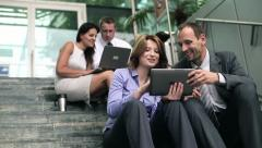 Young business people with tablet computer on stairs by office building HD Stock Footage