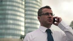 Young handsome businessman talking on mobile phone in the city HD Stock Footage