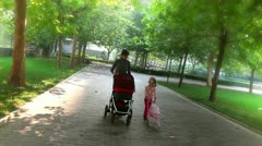 Mother and daughter pushing baby strollers in a park Stock Footage