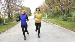 Two woman talking and jogging Stock Footage