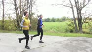 Stock Video Footage of two smiling woman running outdoors in autumn