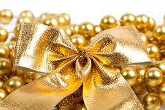 Golden christmas bow and beads Stock Photos