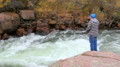 Slow motion high angle shot of young man fishing in rushing river Stock Footage