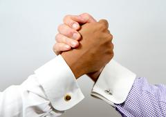 Handclasp between smartly dressed black and white business men - stock photo