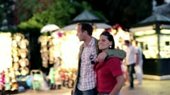 Young couple walking together in night city, steadycam shot - stock footage