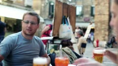 Young man drinking beer in the restaurant, outdoors Stock Footage
