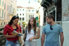 Three friends of tourist looking to guide-book in the old town Stock Footage